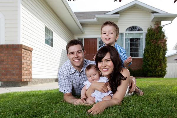 Familia delante de casa con un bebé